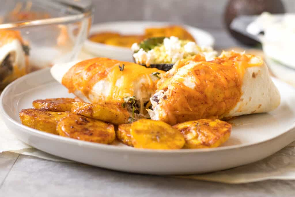 enchilada cut in half on a plate with fried plantains