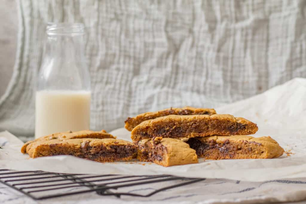 peanut butter chocolate chip tahini bars with a glass of milk