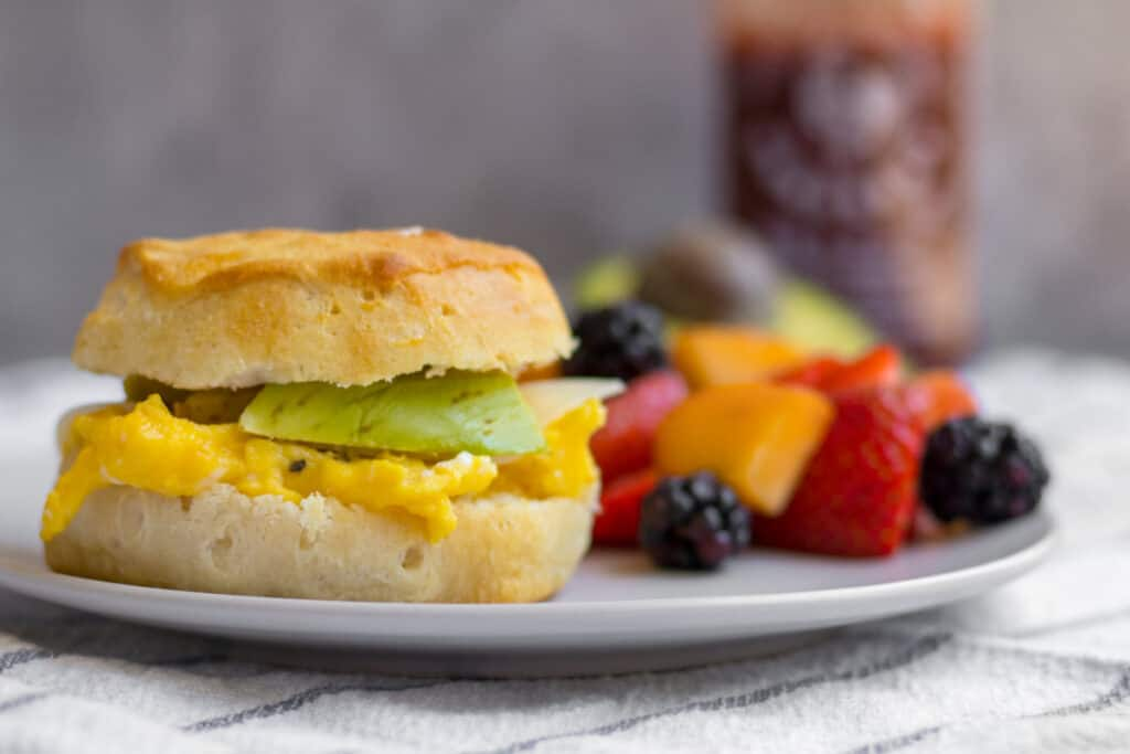 egg and cheese sandwich on a plate with fruit