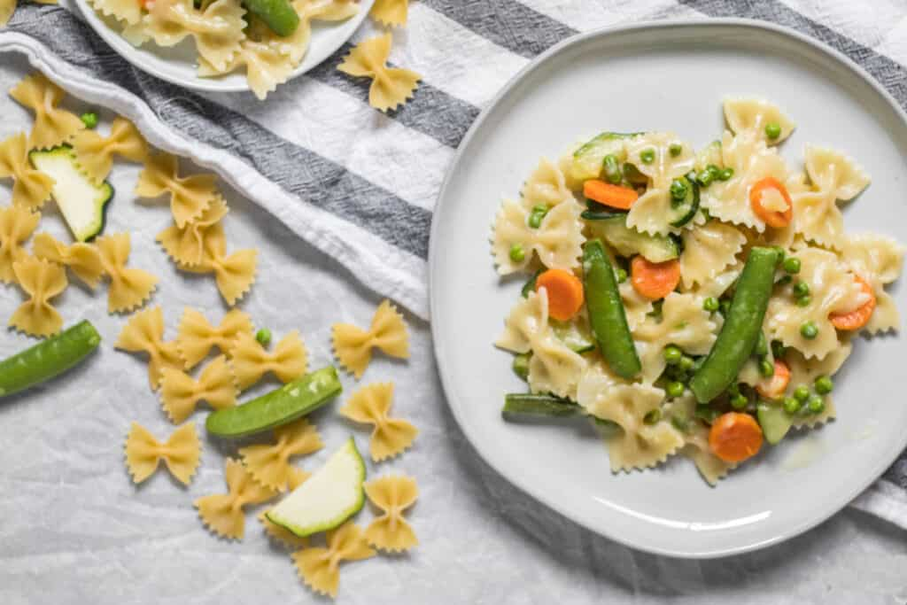 pasta primavera on a white plate with ingredients around it