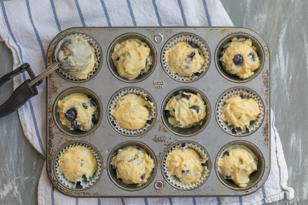 muffin batter being scooped into a muffin tin