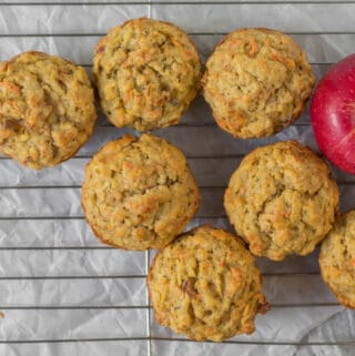 muffins on a cooling rack with 2 apples