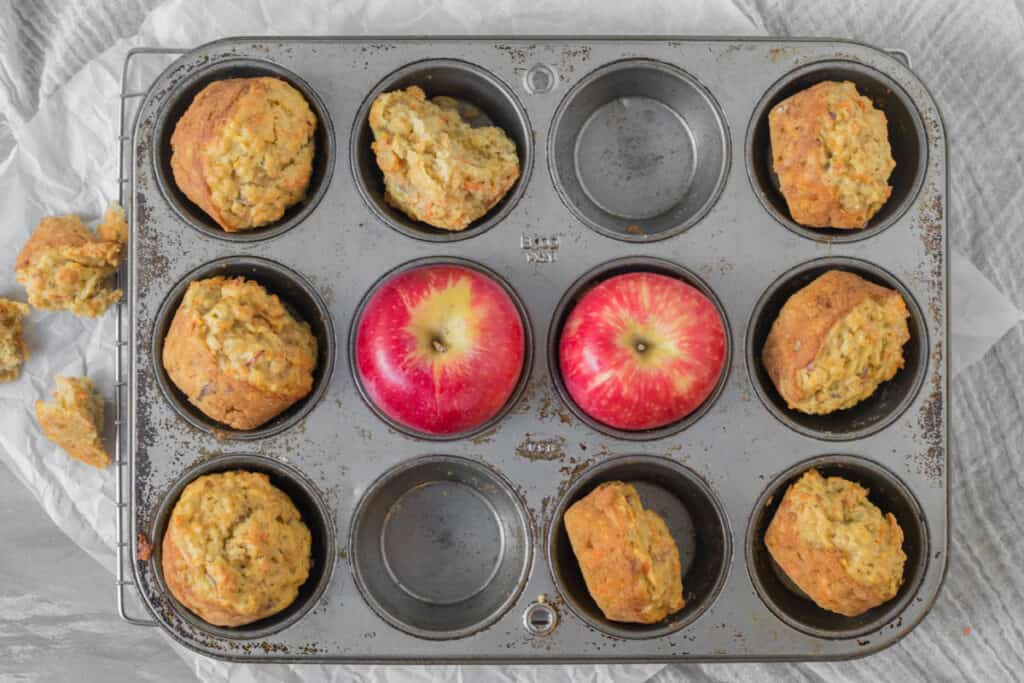 apple carrot muffins in a muffin tin with apples
