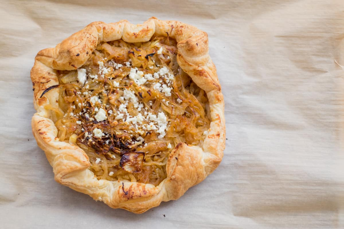 caramelized onion and goat cheese tart on parchment paper