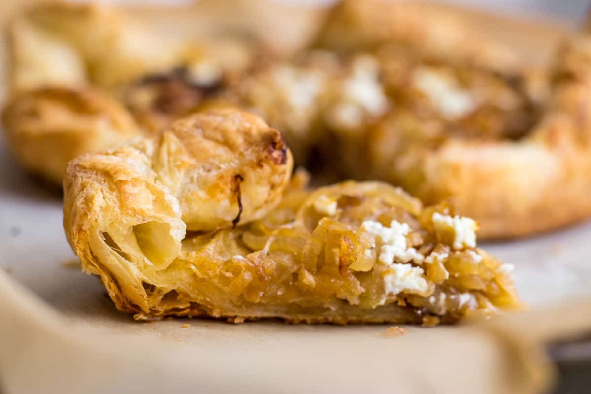 a slice of caramelized onion and goat cheese tart on a sheet pan