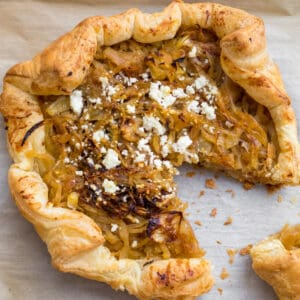 caramelized onion and goat cheese tart with a slice cut out of it