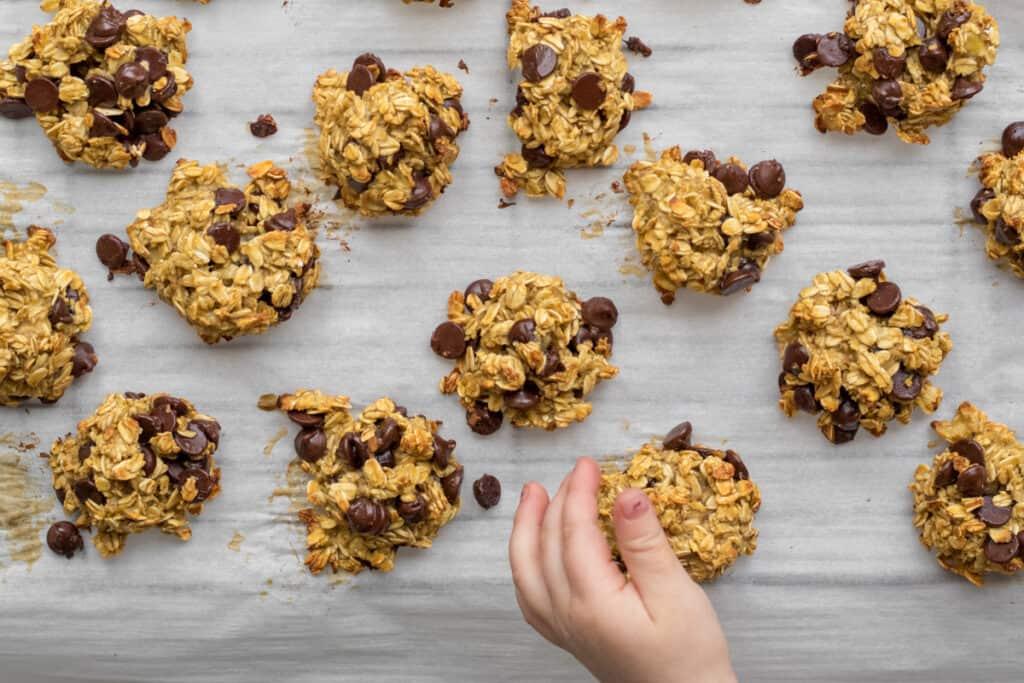 kids hand grabbing a cookie from baking sheet