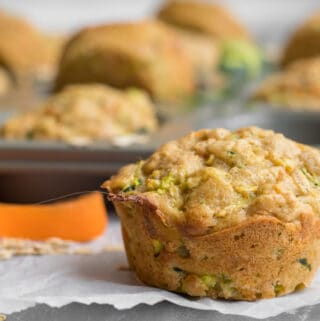 carrot zucchini muffin in front of muffin tin