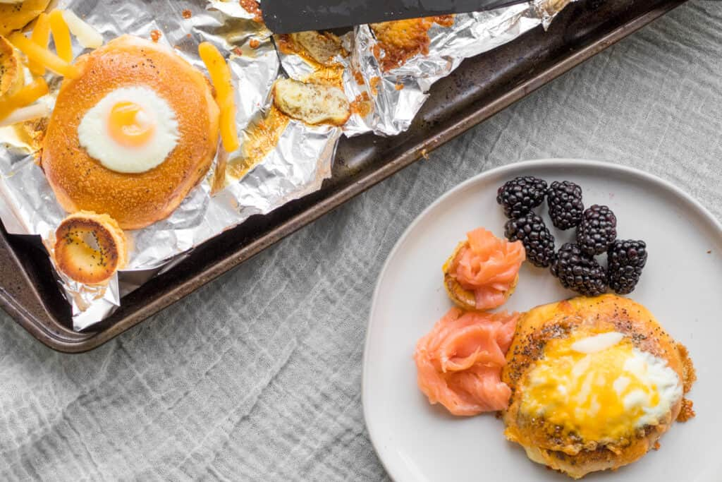 bagel egg in a hole on a plate with lox and fruit with sheet pan in the back.