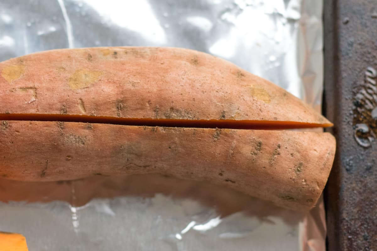 sweet potato cut lengthwise on a foil lined pan