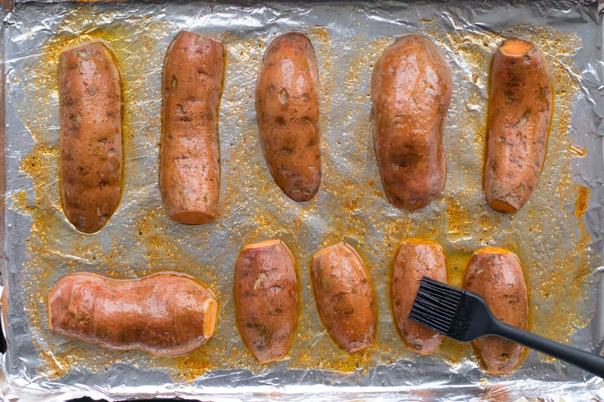sweet potatos on a baking sheet ready to roast