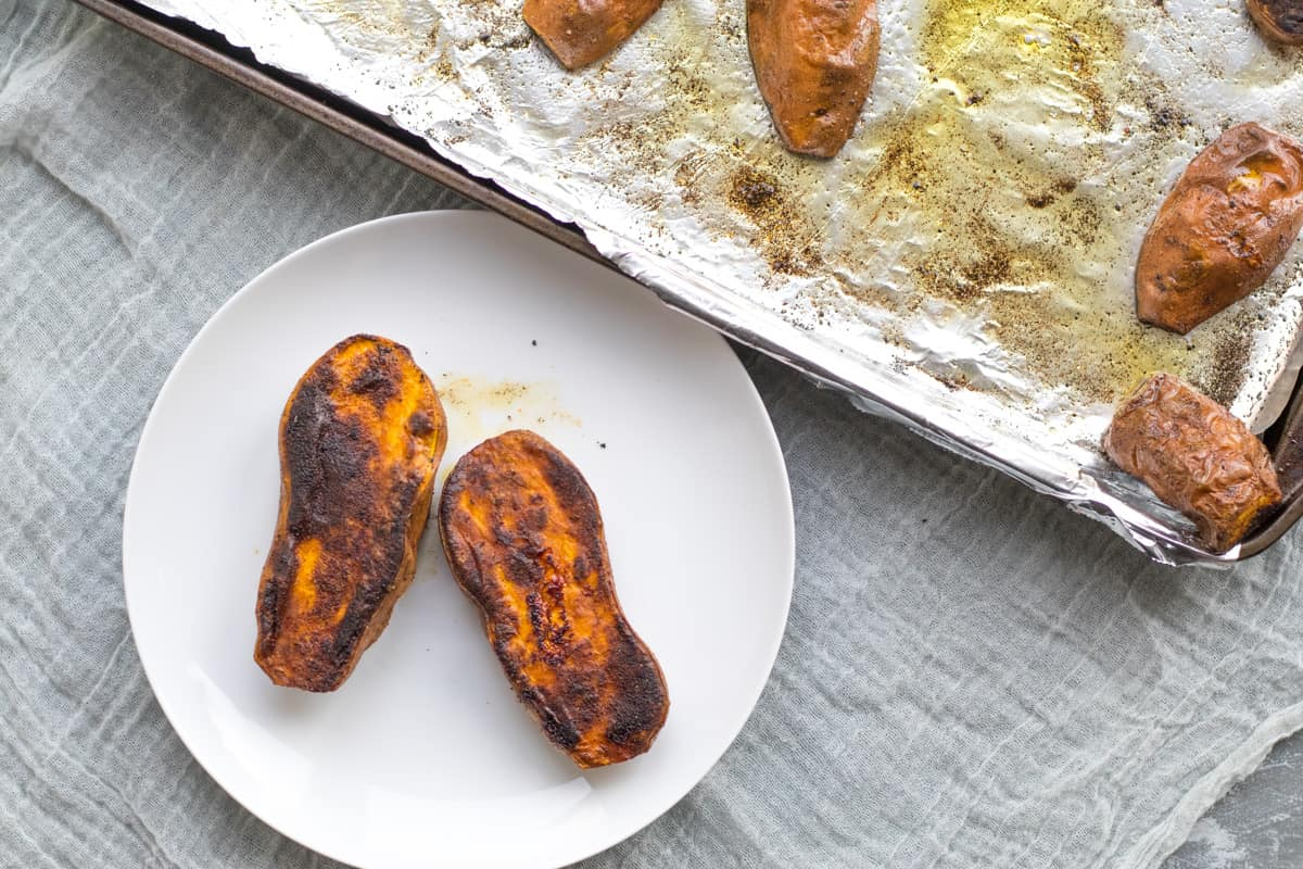 two roasted sweet potatoes on a white plate