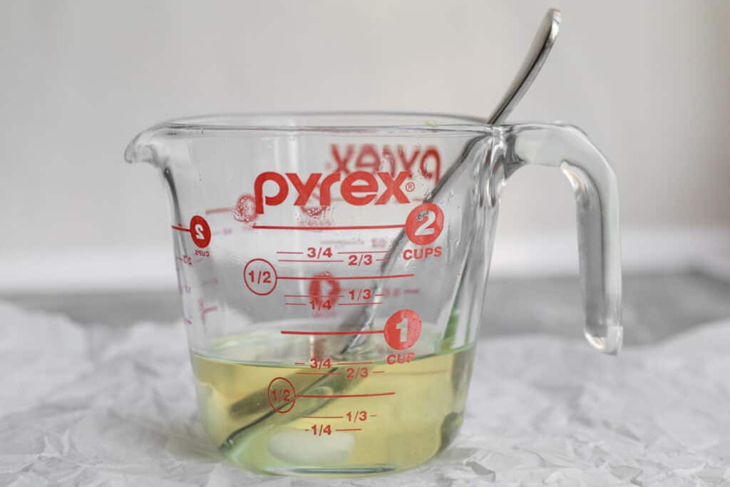 melted coconut oil in a measuring cup