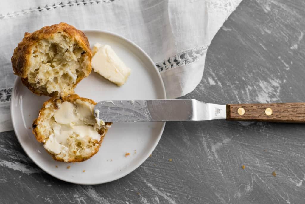 mini spatula buttering a farfel muffin