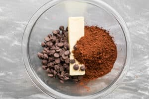 chocolate chips, butter and cocoa powder in a glass mixing bowl