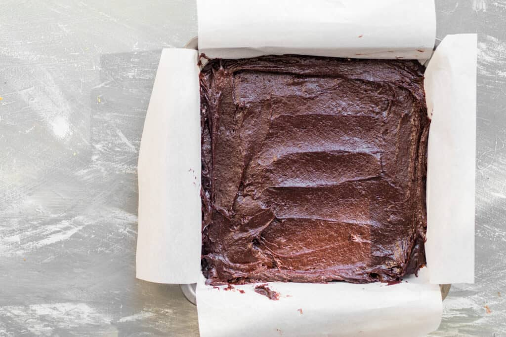 brownie batter in a pan with parchment paper