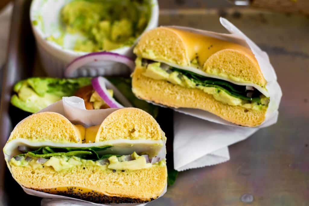 avocado bagel sandwich cut in half in parchment