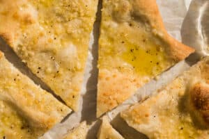 olive oil drizzled on sliced pizza