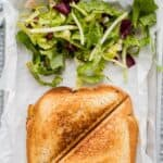 pin for pinterest with grilled sandwich and salad on parchment paper