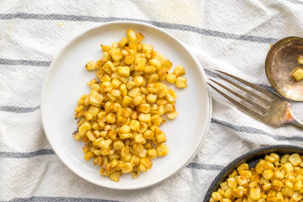 corn on a white plate with a fork