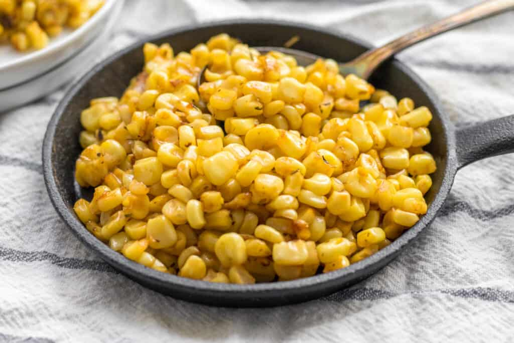 charred corn in a small skillet with a spoon