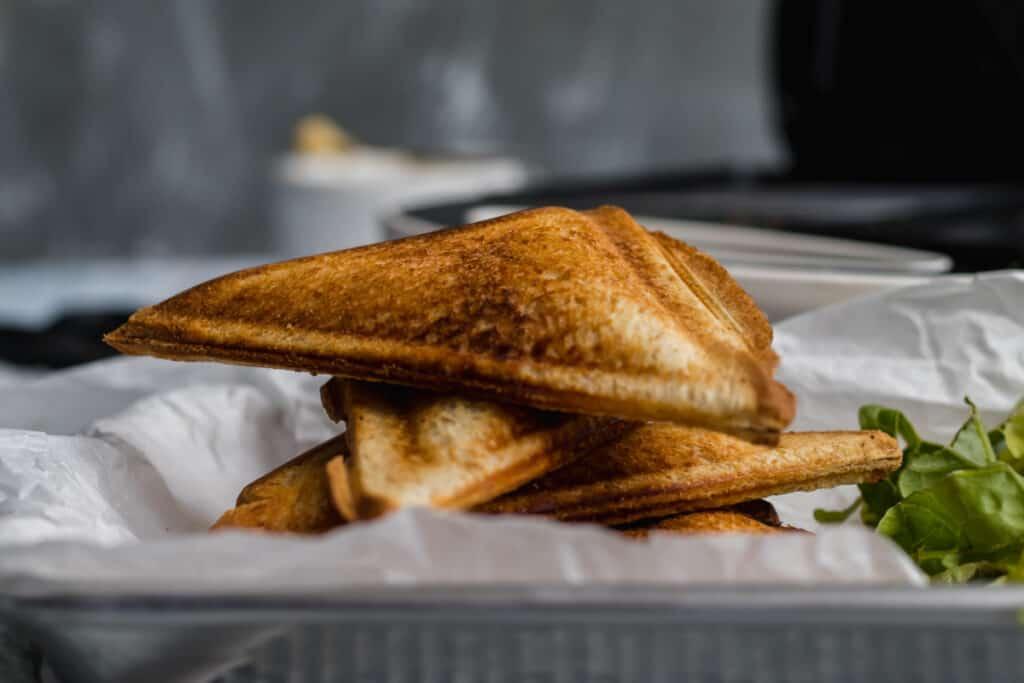 stacked toastie sandwich with sandwich maker in background