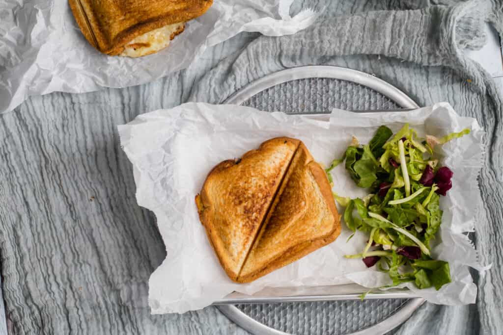 cheese toastie on a parchment paper tray with salad