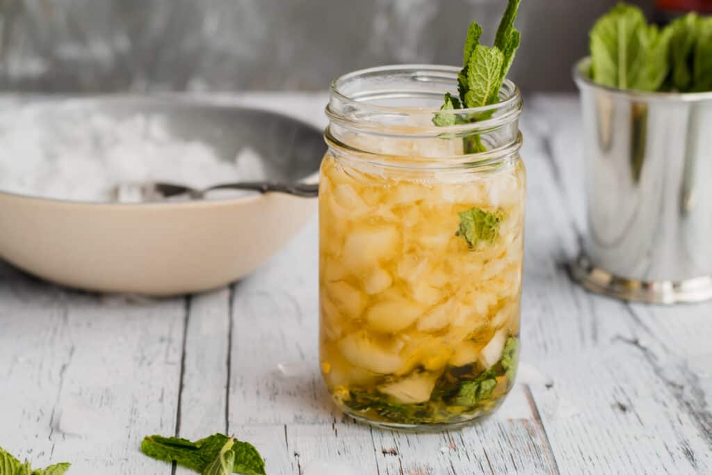 mint julep in mason jar with crushed ice in a bowl