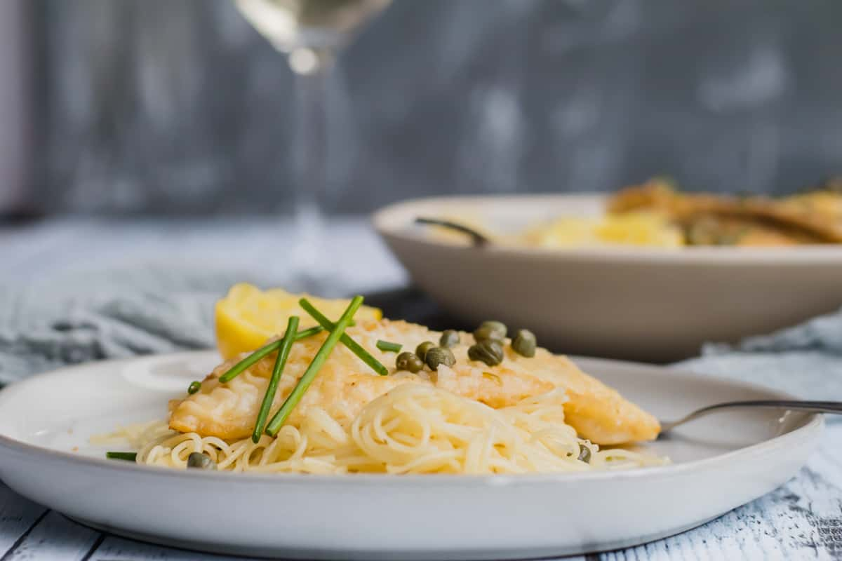 fish piccata on a white plate with glass of wine in background