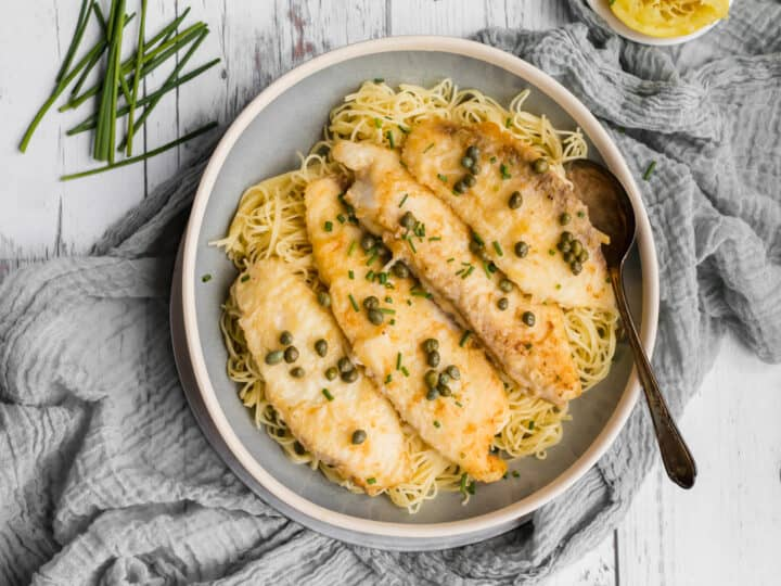 tilapia piccata in a serving dish over pasta with a spoon