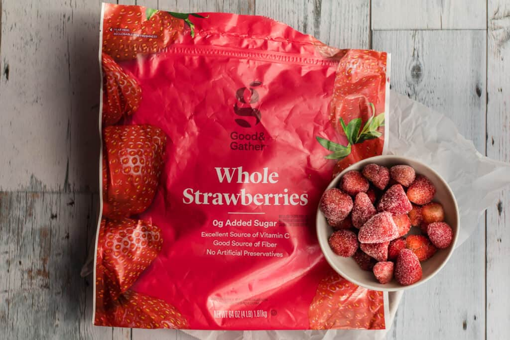 package of frozen strawberries with fruit in a bowl