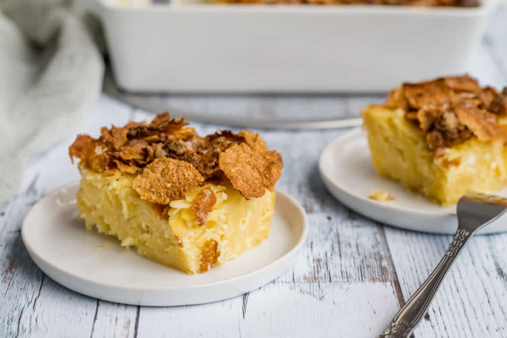 two pieces of noodle  kugel on white plates