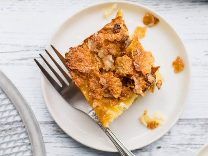 one piece of kugel on a white plate with a fork