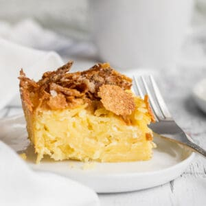 noodle kugel on plate with a fork and mug in background