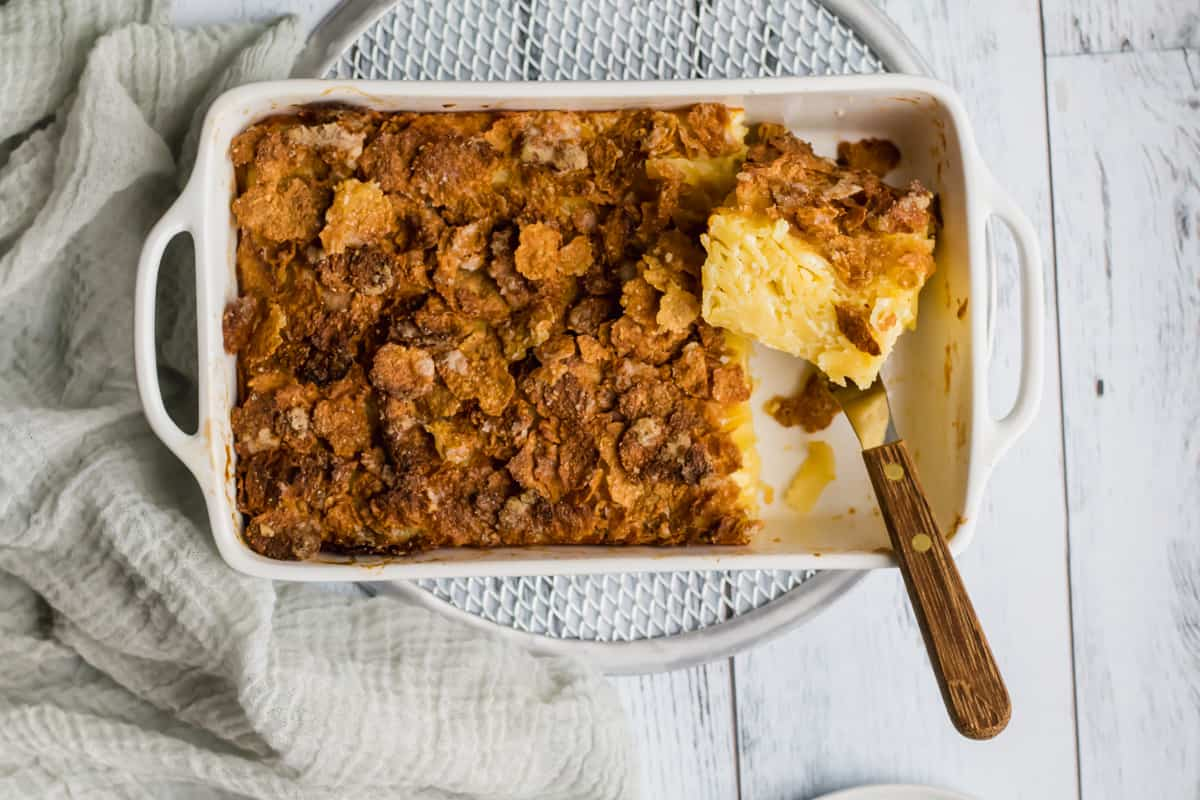 noodle kugel in a white baking dish with a piece cut out