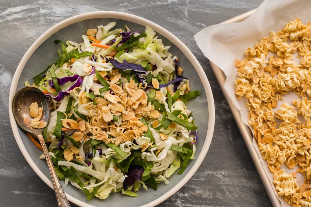 asian cabbage crunch salad in a bowl with baking pan of crunch topping next to it
